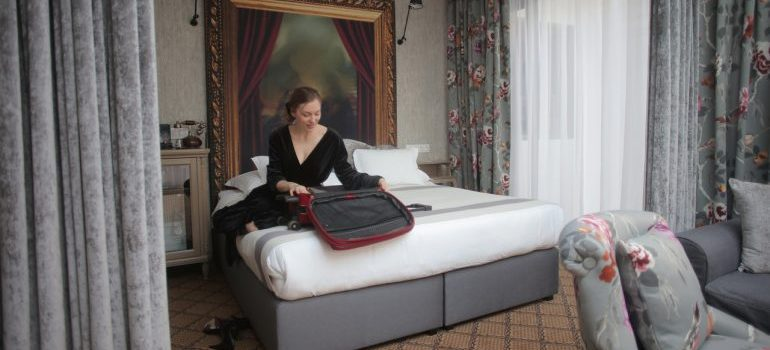 A woman sitting on her bed packing her suitcase.