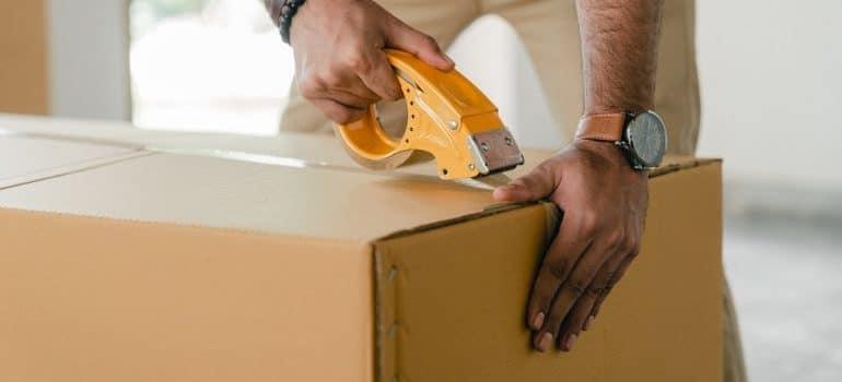 A man closing a moving box