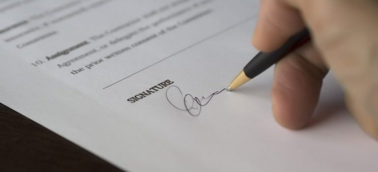 A hand signing a paper