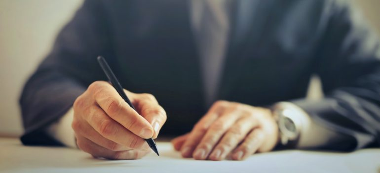 A professional man in a suit signing a contract
