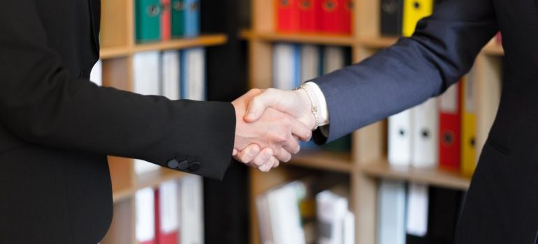 Two people in black suits shaking hands
