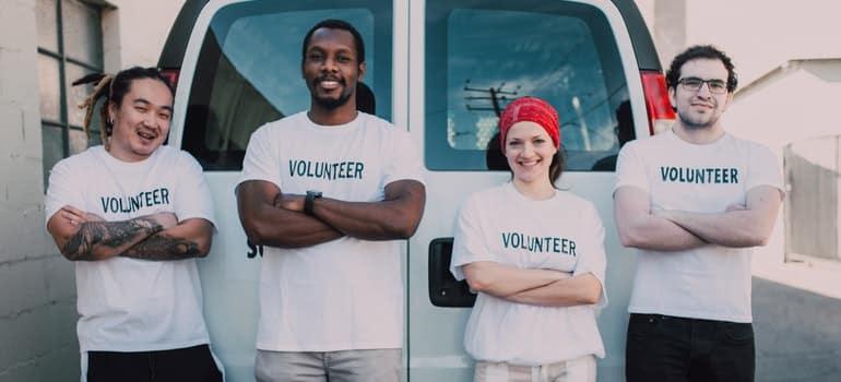 Four volunteers standing in front of van