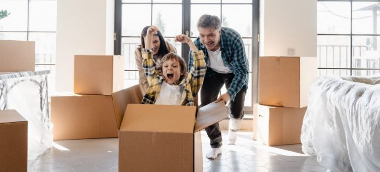 family having fun with moving boxes as a way to prepare your kids for a move