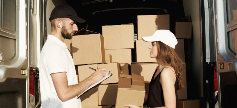 A mover and a woman working together with boxes