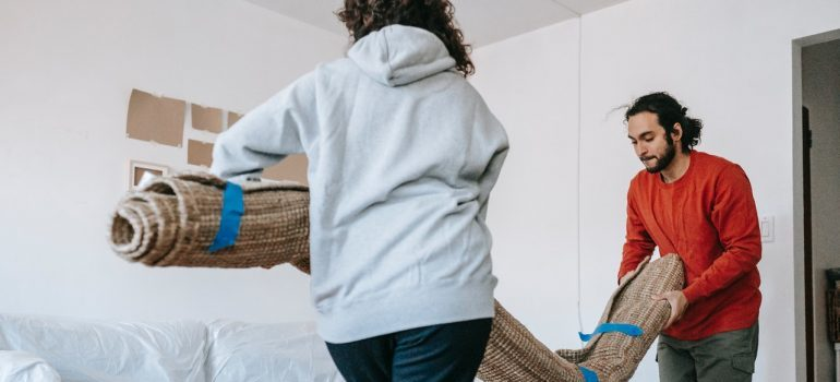Two people carrying a rug into a room