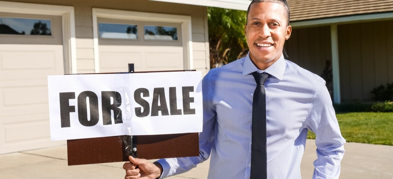"""Man holding """"For sale"""" sign!"""
