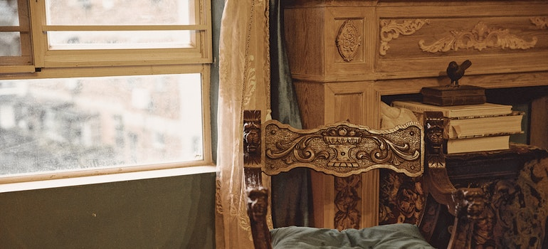 Wooden antique, carved armchair and fireplace