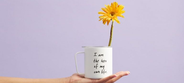 A hand holding a mug with a saying on it and a flower in it