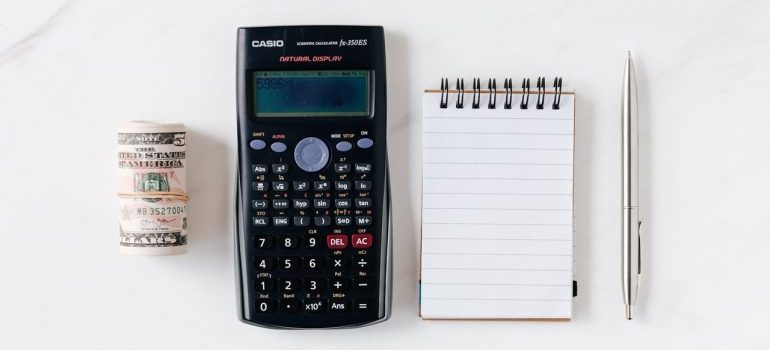 Calculator, money roll, notebook and a pen on the table.