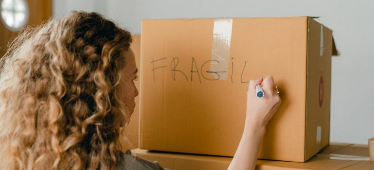 A woman writing on the cardboard box with a marker that it's fragile.