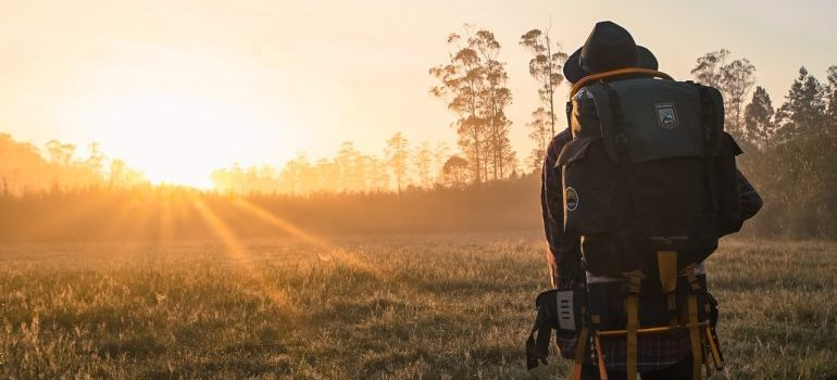 A person in the sunset or sunrise backpacking
