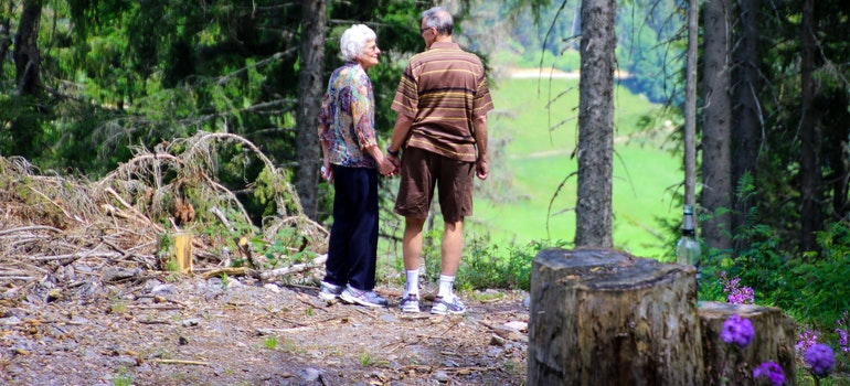 Two seniors standing in forest