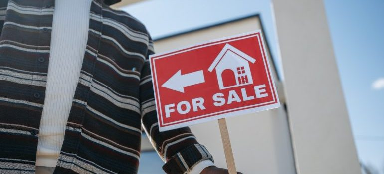 A man holding a sign for sale in front of a house.