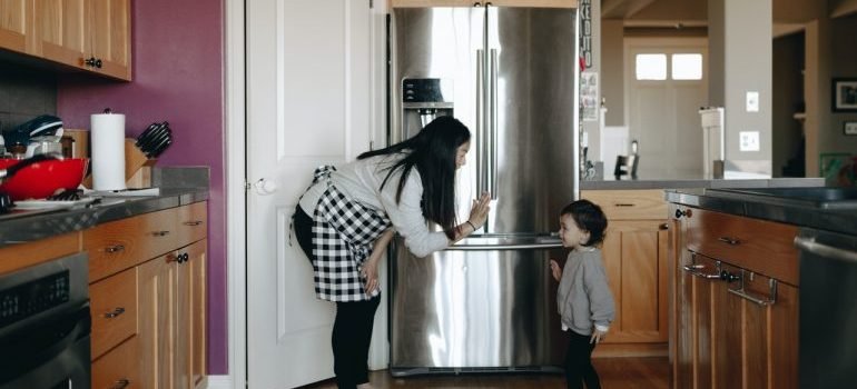 A woman talking to her son about moving large kitchen appliances