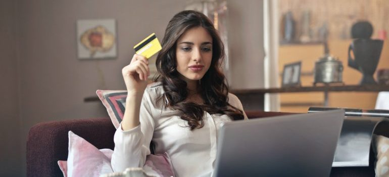 A woman holding a card in her hand and buying new things because she managed to declutter before relocation