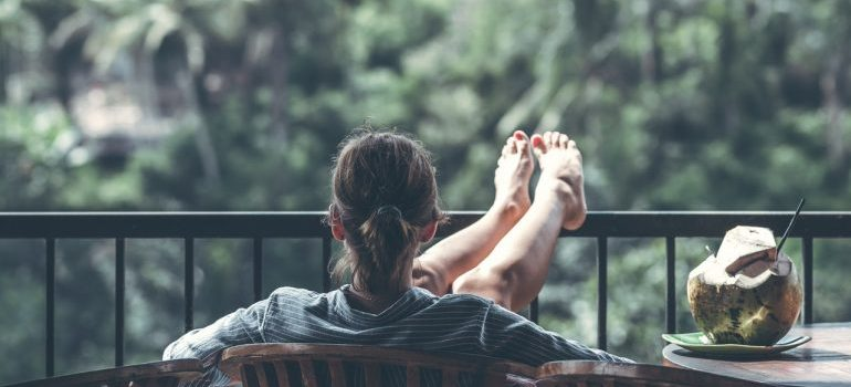 A woman sitting on the balcony with legs on the fence, relaxing.