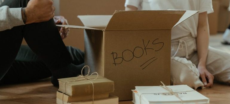 Two people unpacking box which is labeled with books.