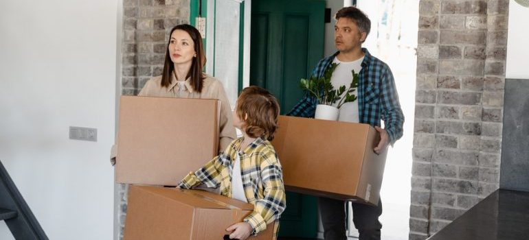 One family carrying boxes after the move into their new home.