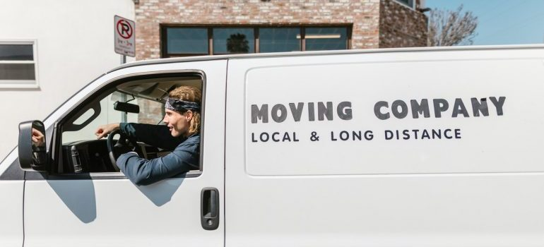 A man working for a moving company driving the van for moving.