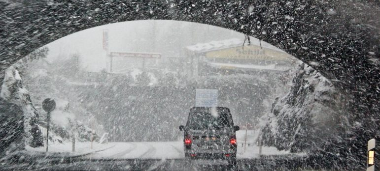 a van passing through a tunnel in a snow which might cause moving delay