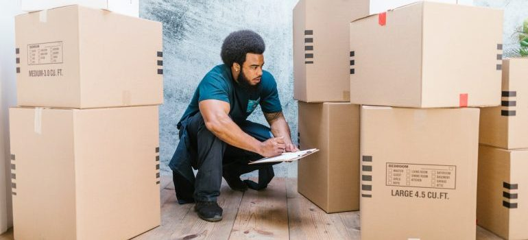 A worker from a moving company checking the boxes for the move.