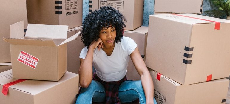 a woman sitting in front of a pile of boxes