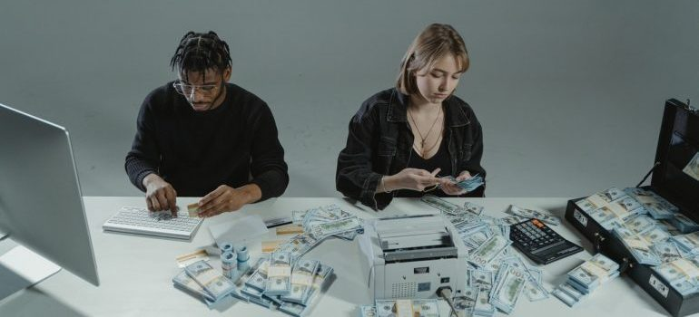 Guy and a girl with a lot of money on the table and computers.