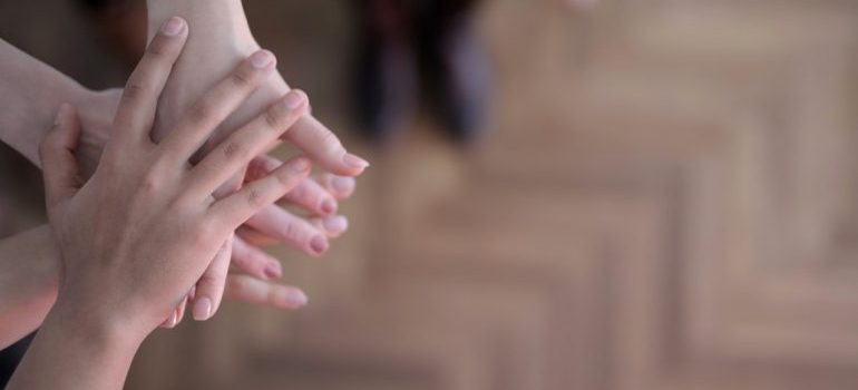 children placing hands to make a deal