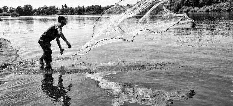 man throwing a fish net as part of summer activities in Hudson