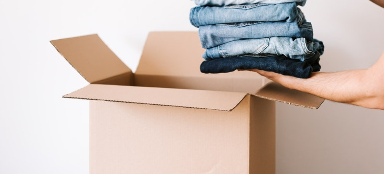 person packing clothes into a box
