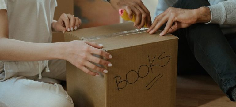 Two persons unpacking a box with books.