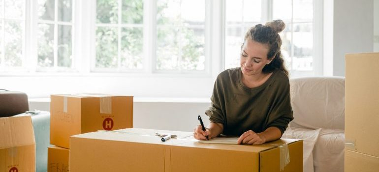 Girl writing a list with bunch of cardboard boxes around her.